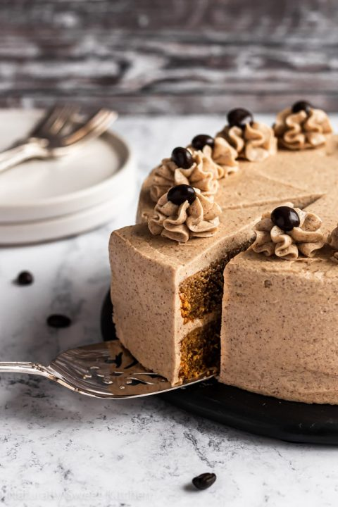 a slice of coffee cake with refined sugar free cinnamon frosting being removed from the platter.