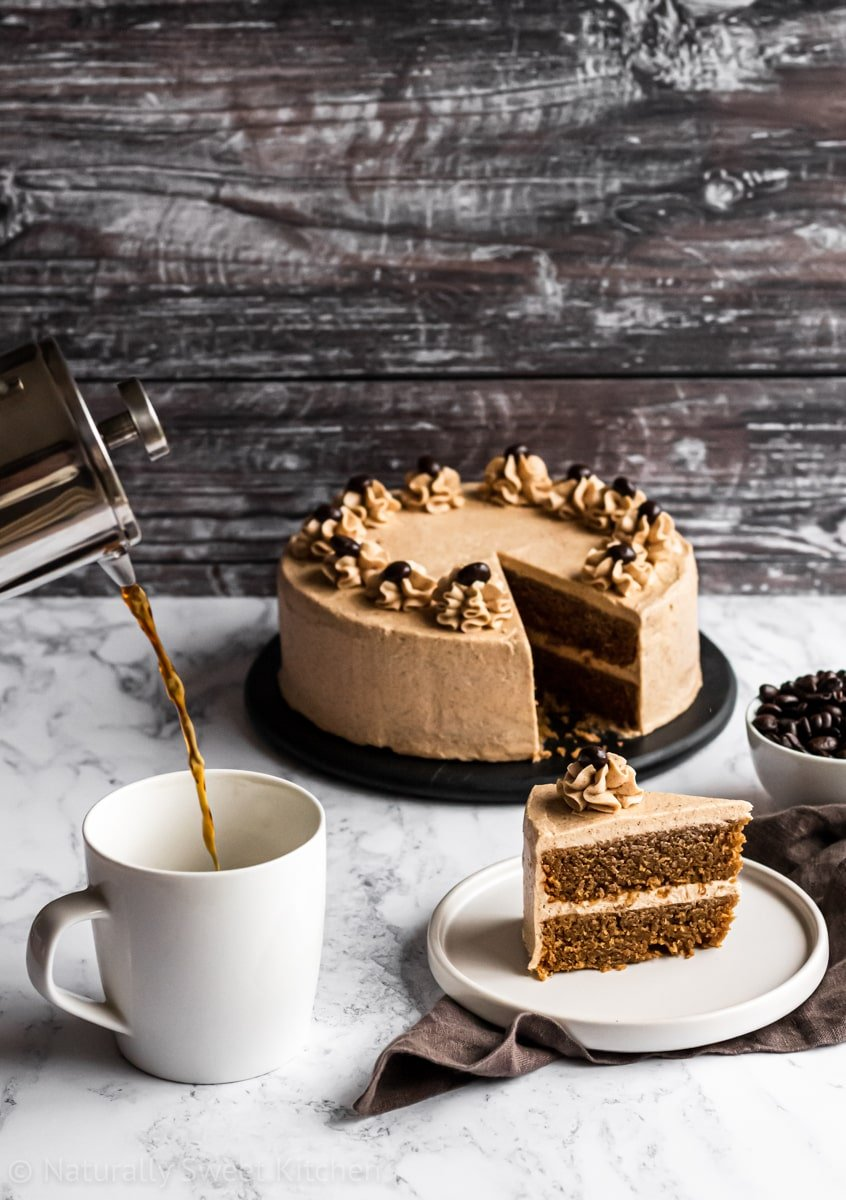 coffee being poured into a mug with a slice of this easy coffee cake recipe on the side. Brown wooden background behind.