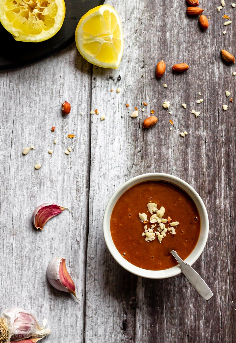 the best peanut sauce ever in a bowl with a metal spoon and crushed peanuts, surrounded by lemon wedges and garlic cloves on a wooden background