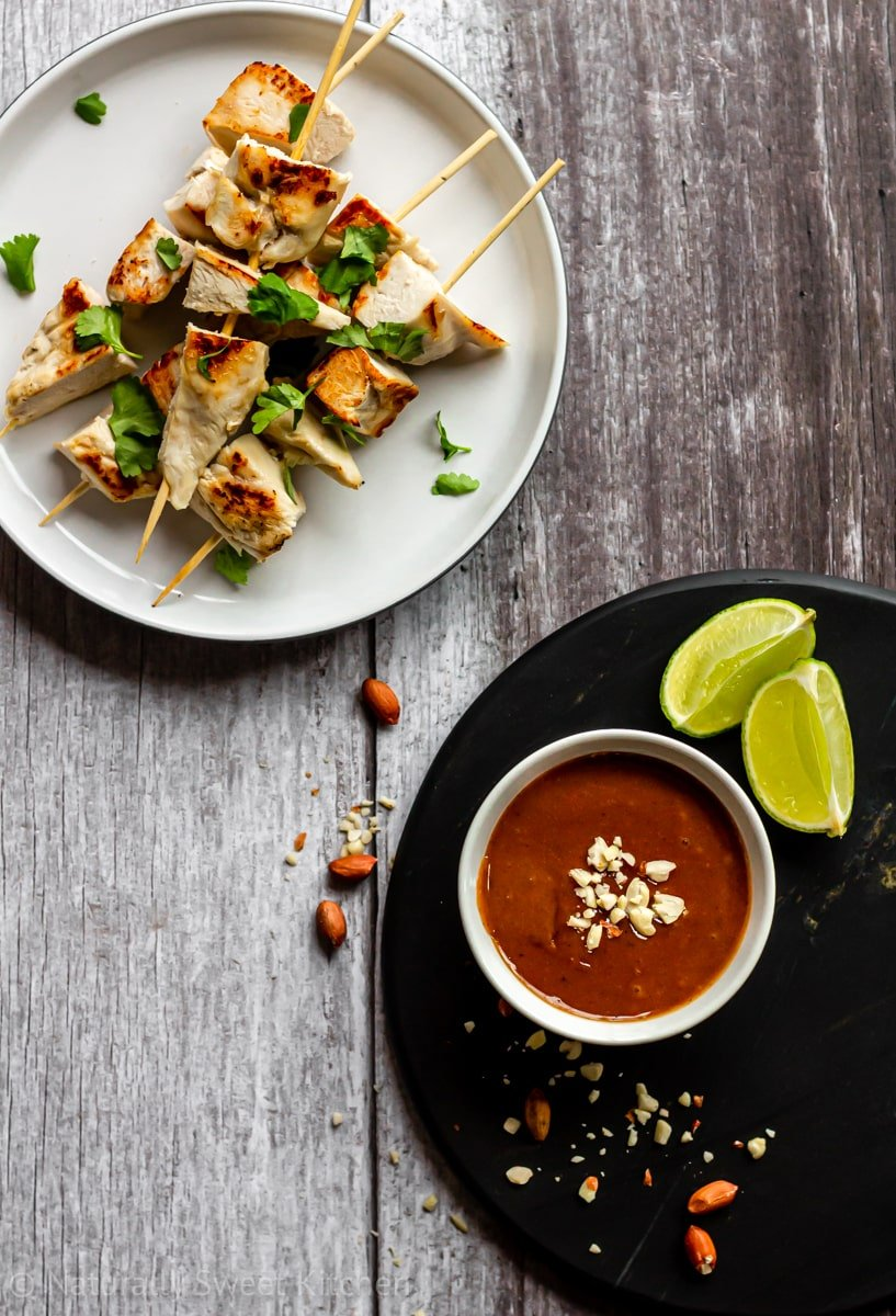 top down view of a plate of chicken satay skewers and a small bowl of peanut sauce with crushed peanuts and lime wedges around it