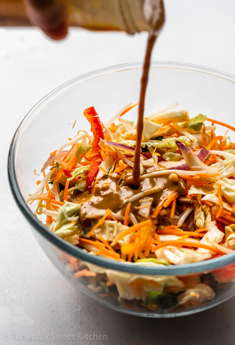 pouring peanut sauce over coleslaw veggies as a dressing