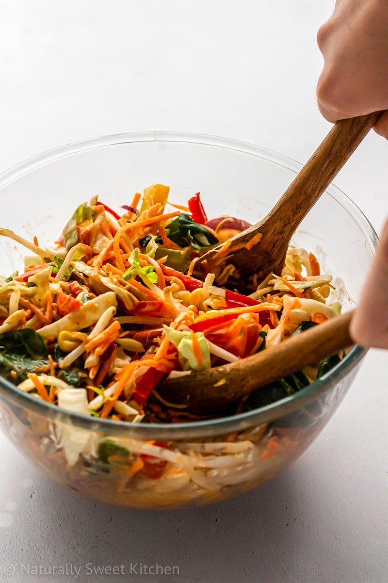 best peanut sauce being tossed with coleslaw veggies using wooden spoons