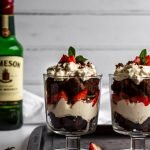 Two serving glasses of chocolate brownie trifle on a dark tray with a bottle of Jameson's Irish whiskey in the background
