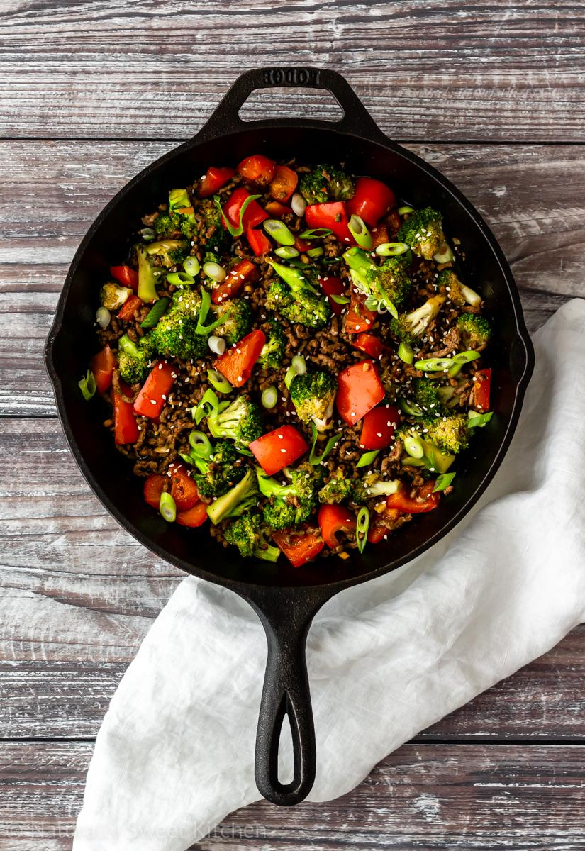 top down shot of refined sugar free easy korean beef bulgogi with broccoli and red peppers on a wooden table with a white linen underneath the pan.