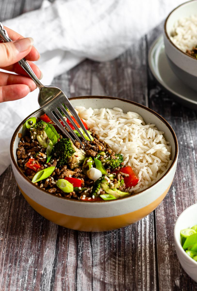 a bowl of easy korean beef bulgogi with vegetables and white rice; a hand is holding a fork poised over the bowl, ready to eat