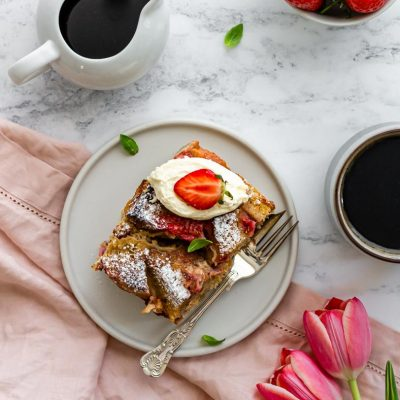 top down shot of a plate of overnight strawberry french toast bake with pink tulips and a pink linen napkin beside it, surrounded by a mug of coffee, strawberries, and maple syrup