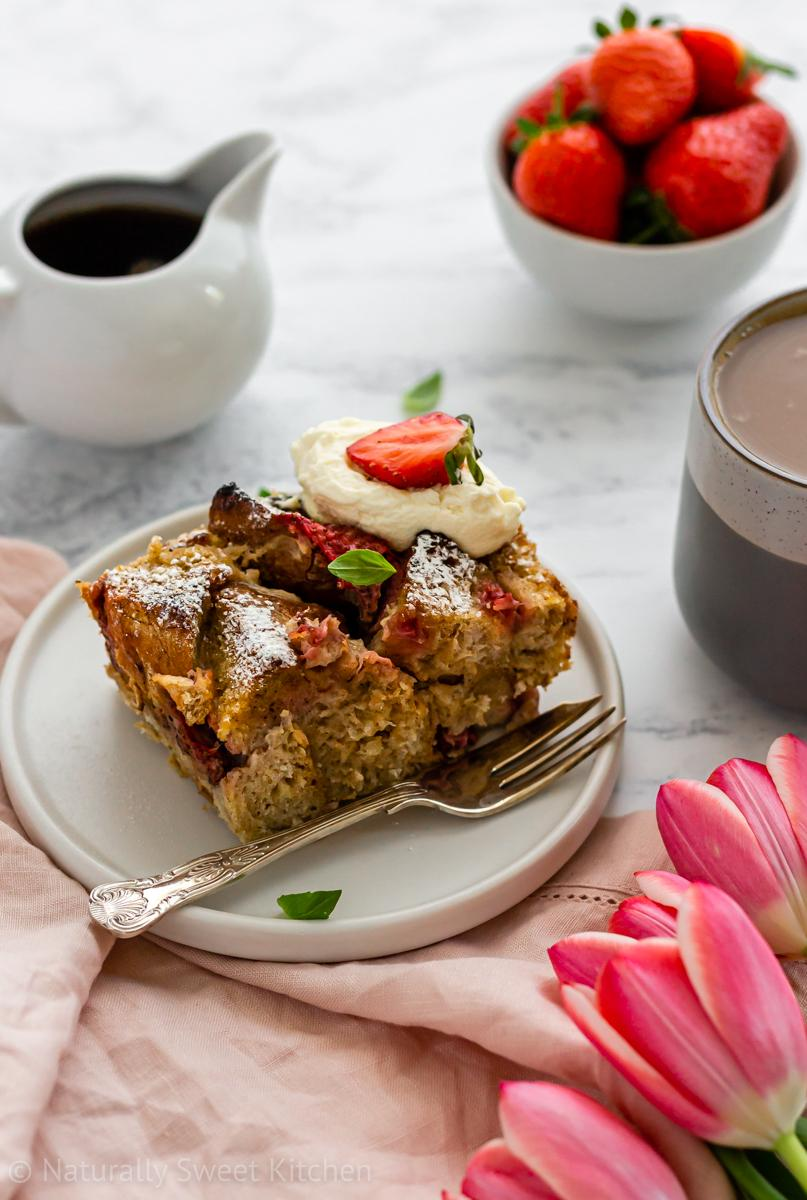 A slice of overnight strawberry french toast bake on a plate, topped with whipped cream and basil. A bowl of strawberries and maple syrup is in the background.