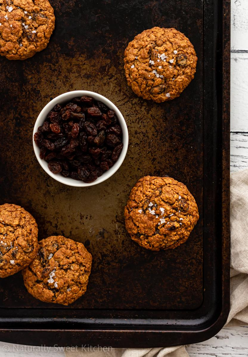 refined sugar free oatmeal raisin cookies topped with sea salt on an antique baking tray with a small bowl of raisins at the centre