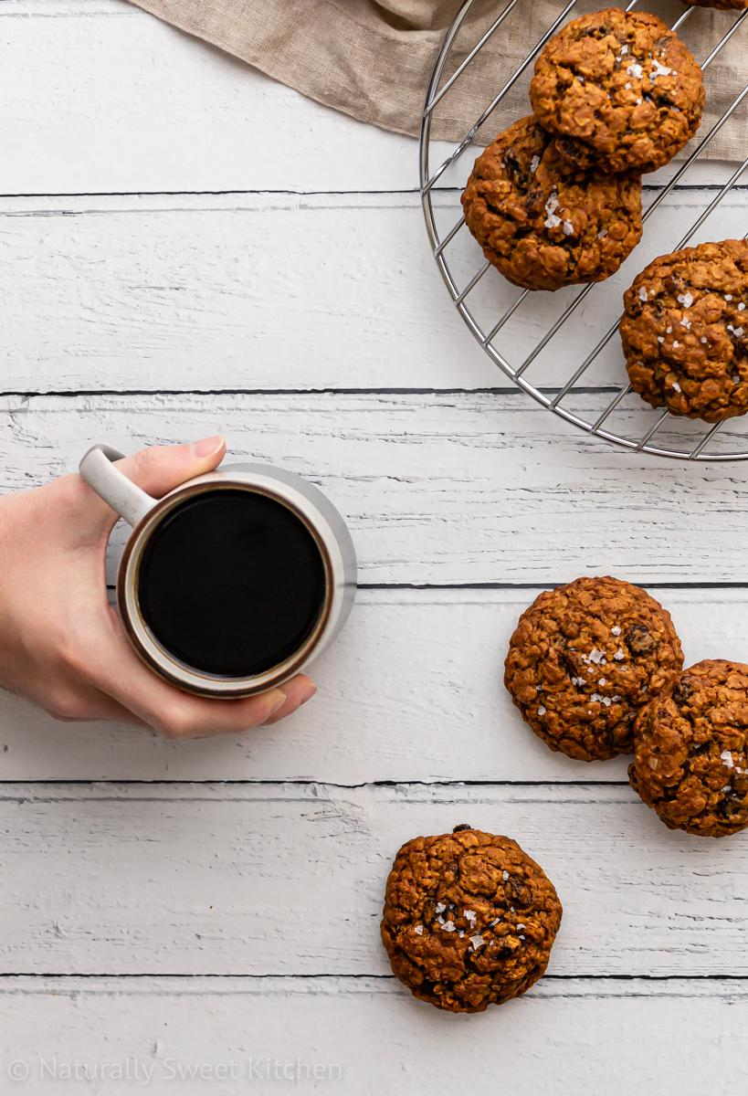 a top down shot of a strewn pile of refined sugar free oatmeal raisin cookies alongside a person holding a cup of black coffee