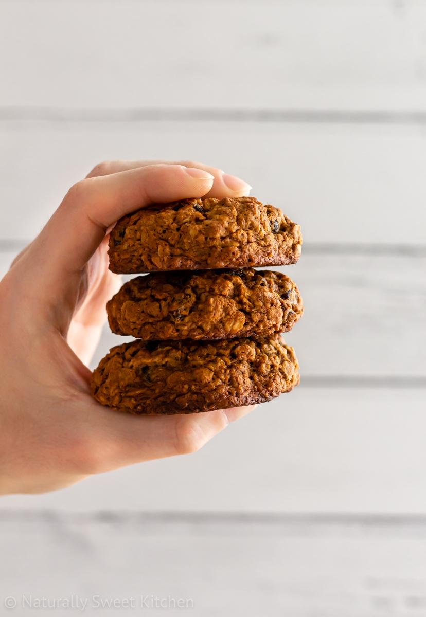 a hand holding a stack of three refined sugar free oatmeal raisin cookies with soft right hand side lighting