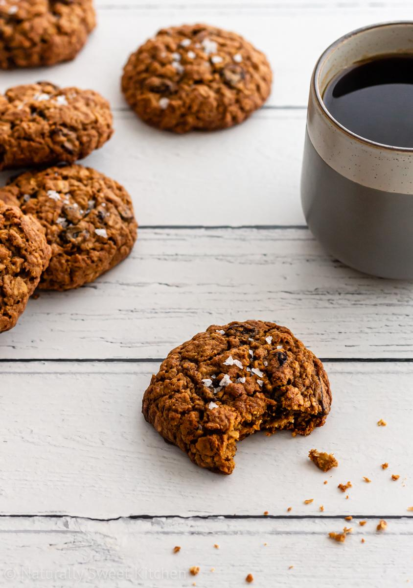 a pile of refined sugar free oatmeal raisin cookies, a mug of black coffee and a cookie with a bite taken out of it on a wooden background