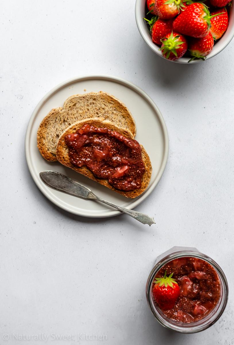 a top down shot of a plate of toast smeared with healthy strawberry chia jam with a bowl of strawberries in the top right corner