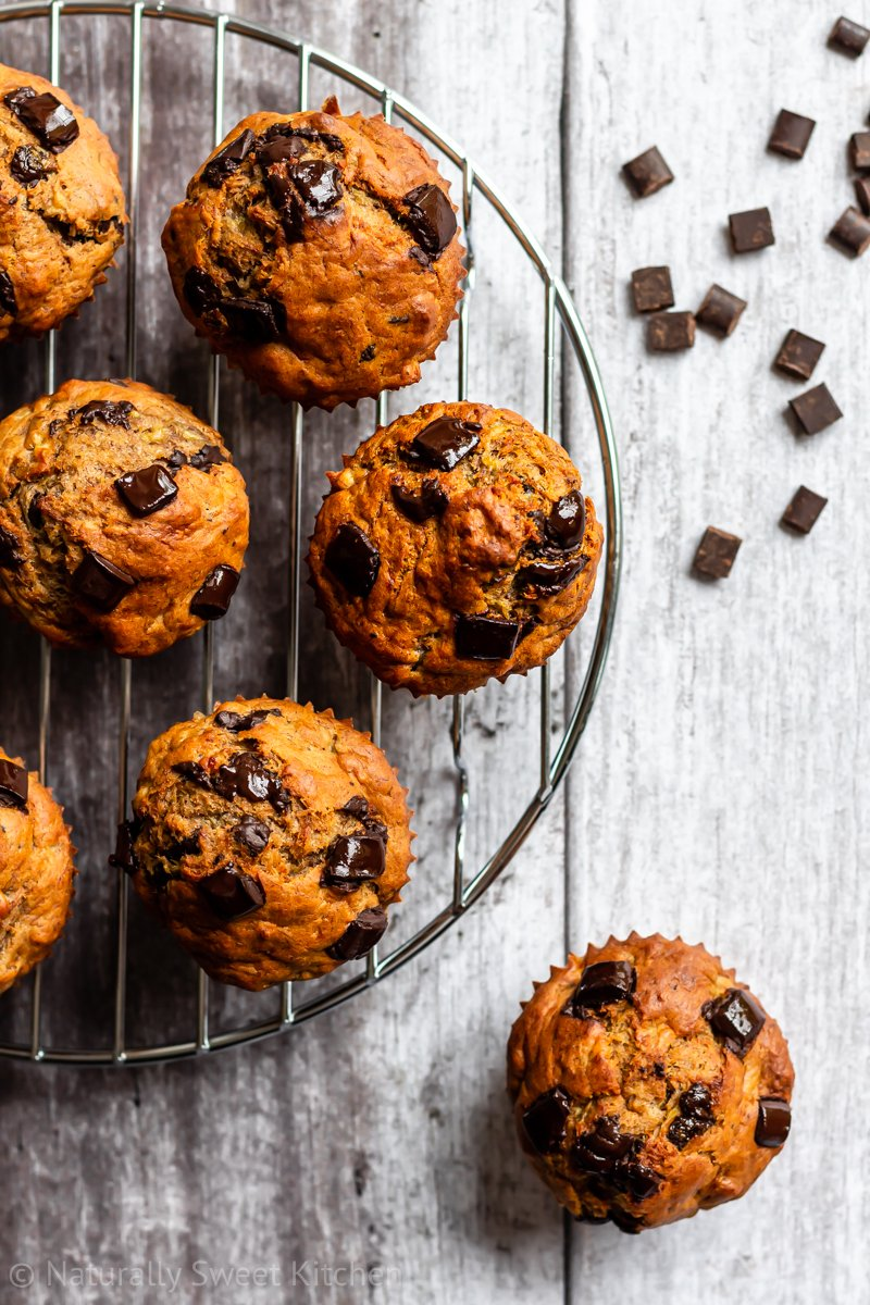 a bunch of no sugar banana muffins on a circular wire rack with scattered dark chocolate chunks in the corner of the image