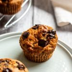 a serving of sugar free banana muffins with dark chocolate chunks on layered plates on a whitewashed wooden background