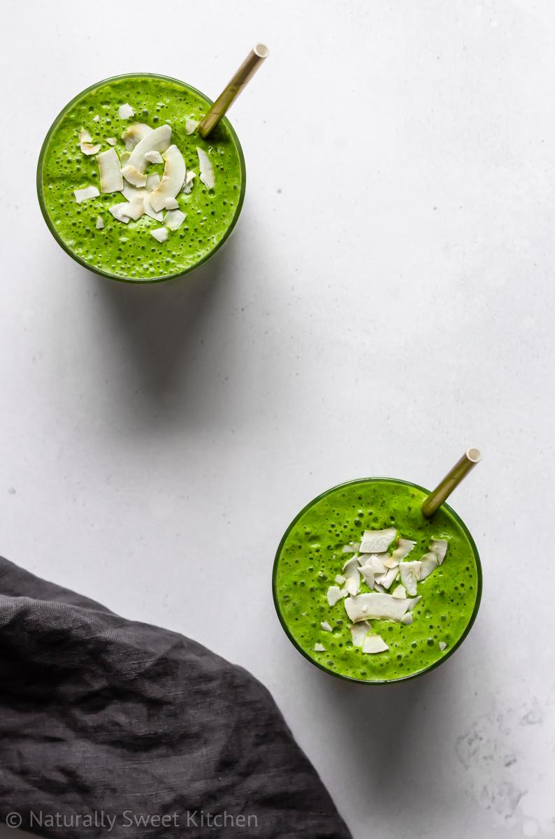 two green pina colada smoothies on a white backdrop with gold straws and toppings of flaked coconut