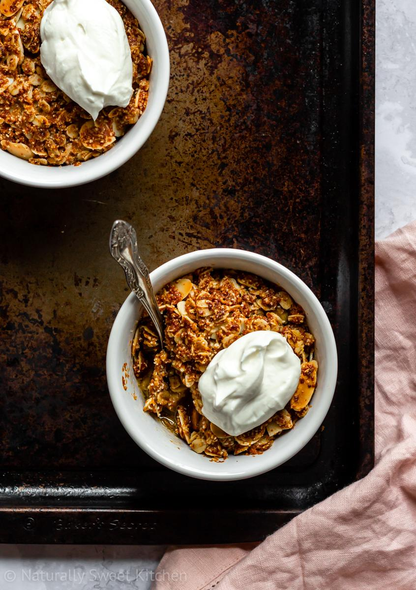 two individual rhubarb and ginger crumbles topped with Greek yoghurt on a dark serving tray with a pink linen