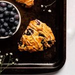 two blueberry scones topped with cardamom glaze on a dark baking tray with tiny flowers and a bowl of blueberries