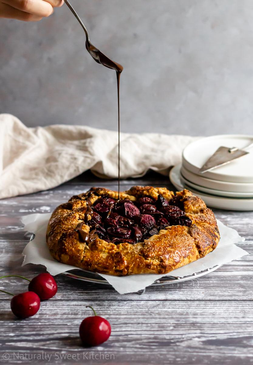 a spoon drizzling melted dark chocolate over a baked cherry galette on top of a wire cooling rack