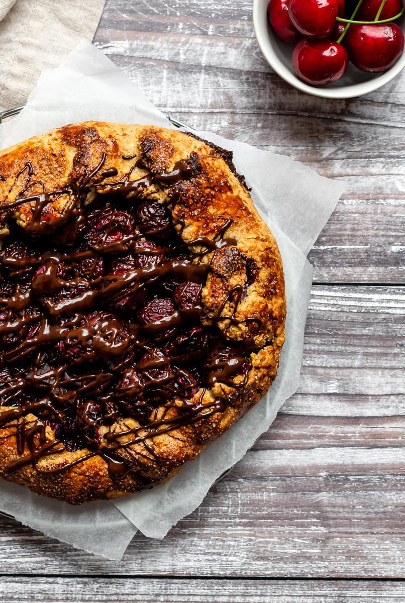 an aerial shot of a naturally sweetened cherry galette drizzled with dark chocolate on white parchment paper. a bowl of cherries is in the upper right corner