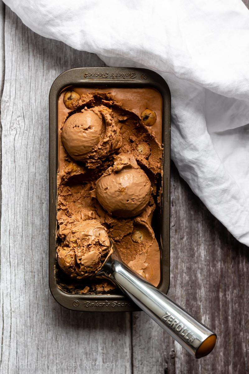 a tin of Chocolate Peanut Butter Cookie Dough Ice Cream with three prepared scoops and a zeroll ice cream scoop ready to serve