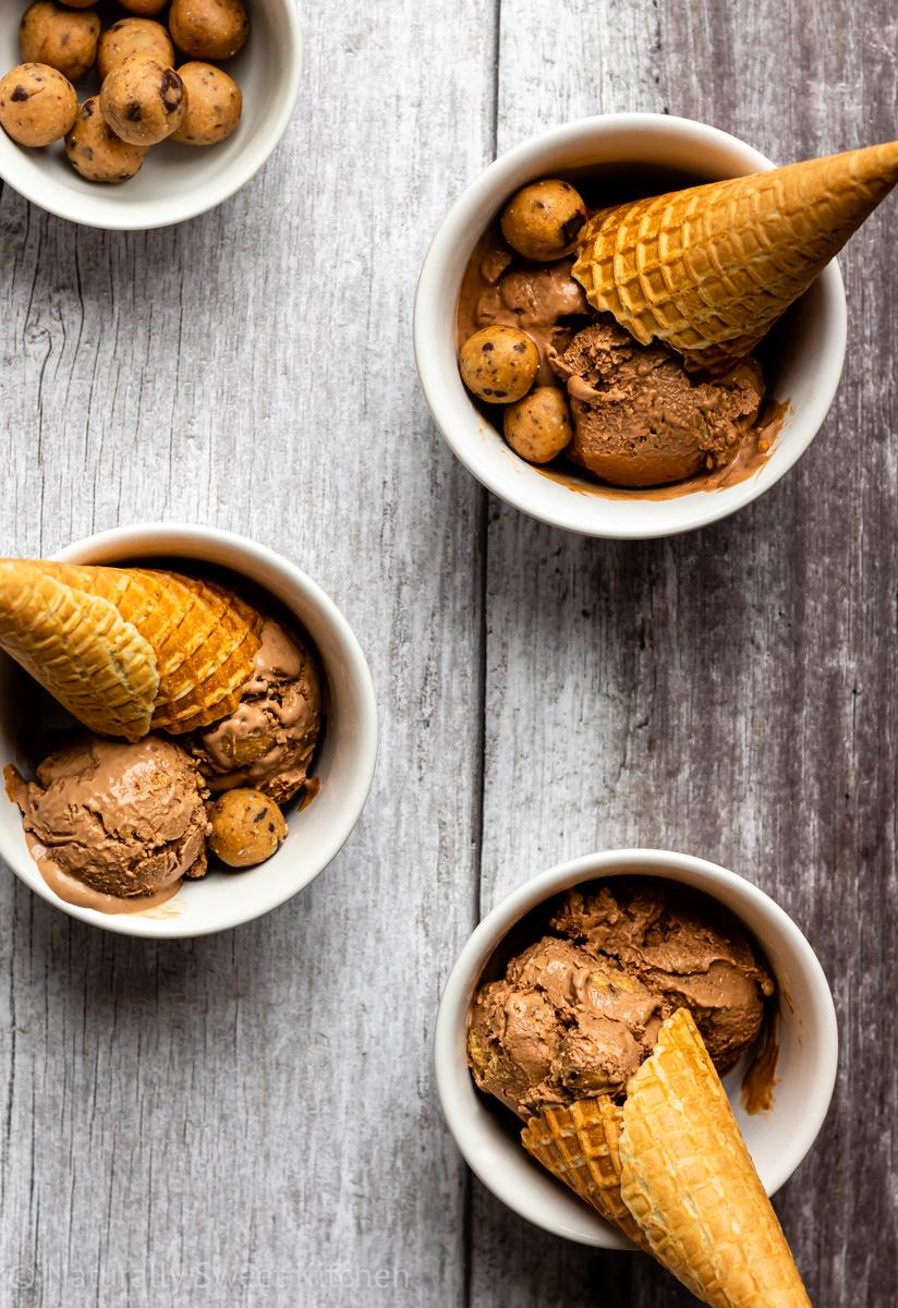 an aerial shot of three bowls of Chocolate Peanut Butter Cookie Dough Ice Cream with waffle cones and a small bowl of cookie dough balls in the corner