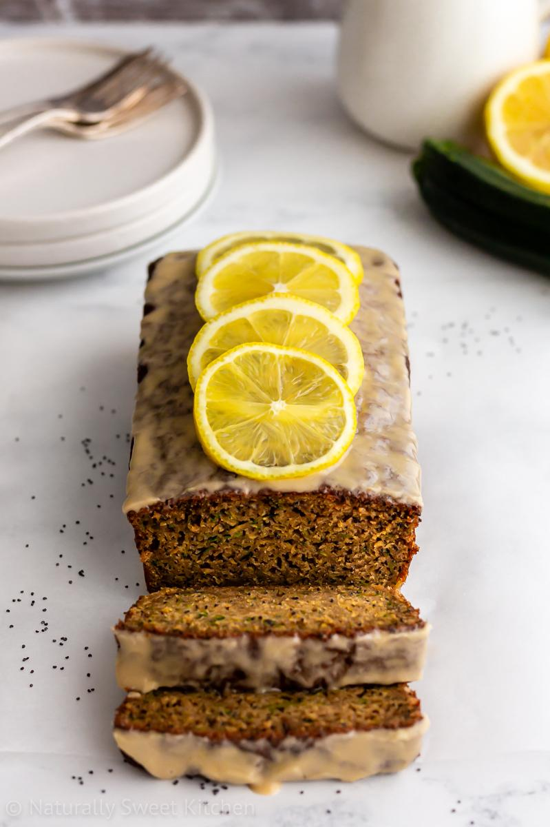A loaf of lemon courgette cake with a few slices cut out on a white background with poppy seeds scattered around