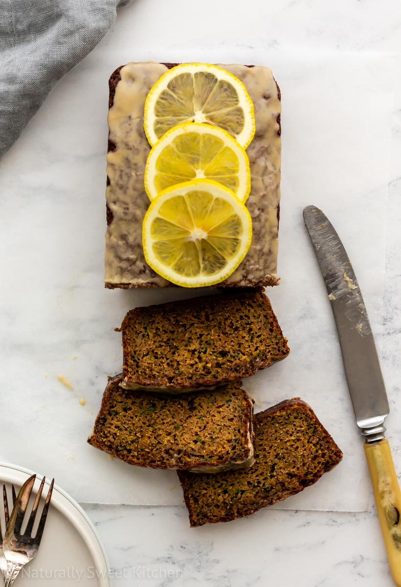 slices of lemon courgette cake laid out next to the full loaf and a knife