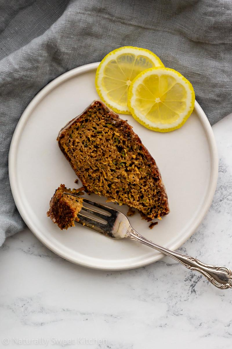A slice of lemon courgette cake on a white plate with lemon slices and a fork taking a bite off of it.