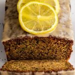 a loaf of lemon courgette cake with a slice cut out on a marble background with poppy seeds scattered around