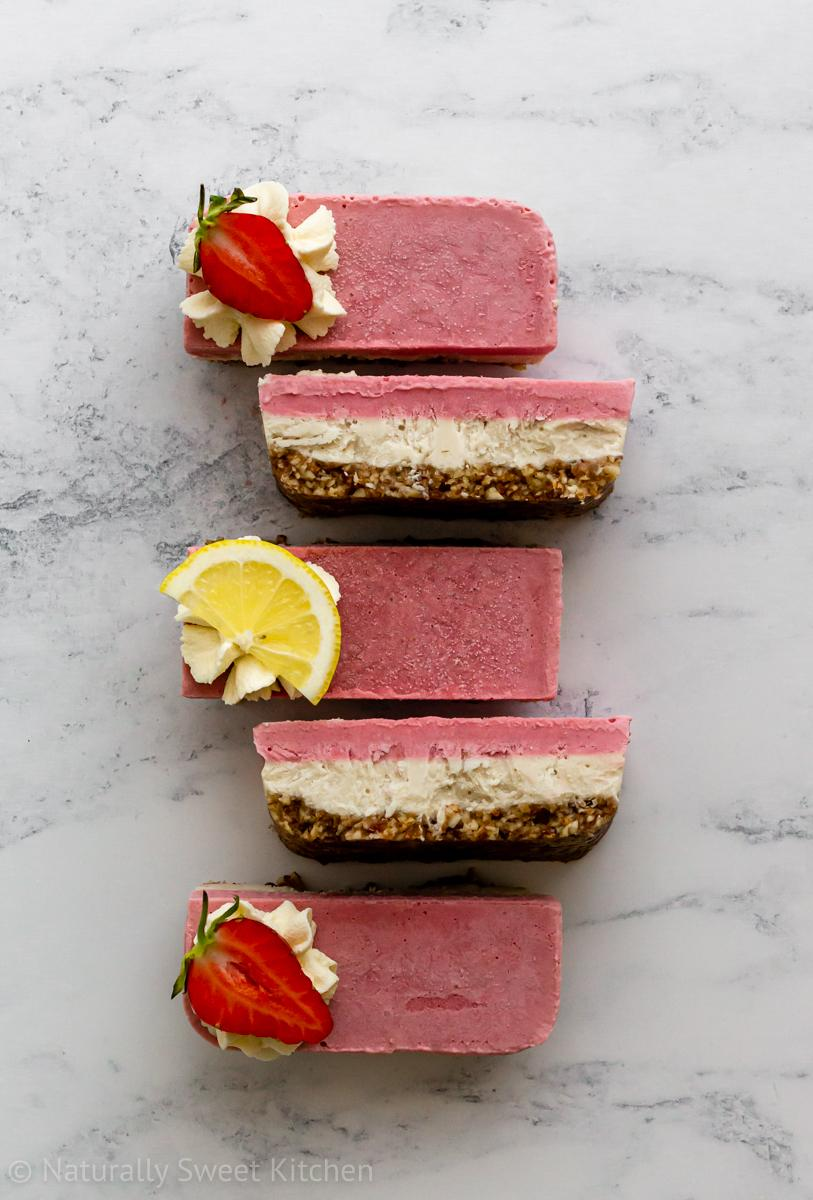 five slices of refined sugar free no bake strawberry lemon cheesecake bars on a white marble background in alternating top and side poses