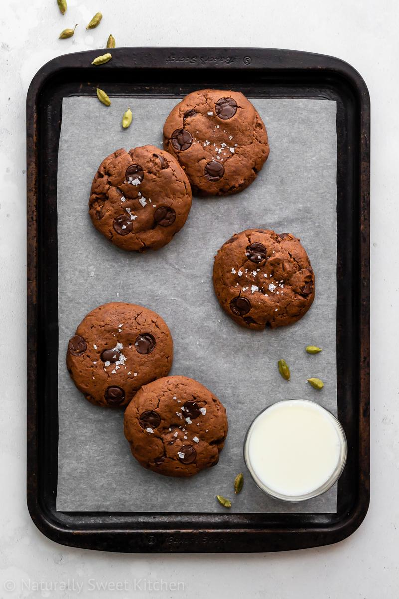 five chocolate chai cookies on a baking tray with a small glass of milk in the lower right hand corner of the straw and scatterings of cardamom pods surround it.