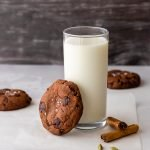 a tall glass of milk surrounded by chocolate cookies topped with sea salt. one chocolate chai cookie is leaning against the milk glass.