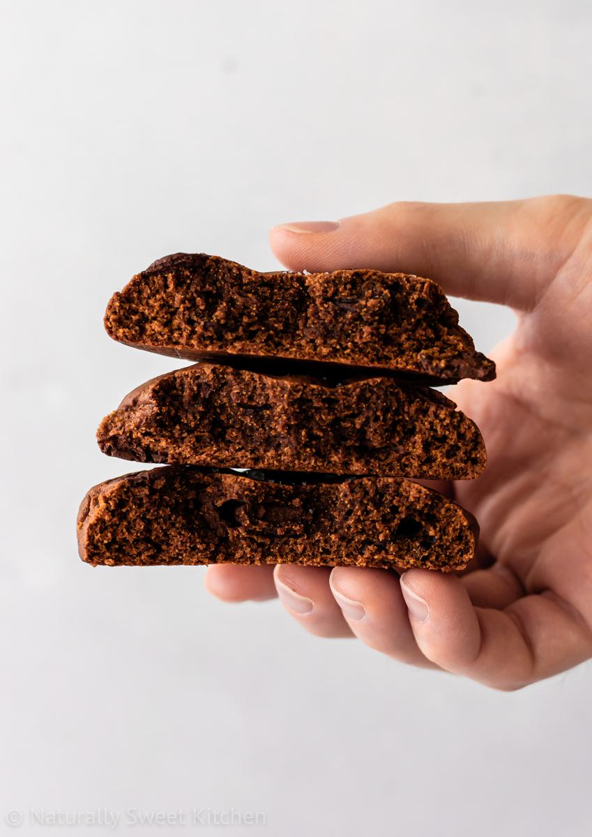 a hand holding a stack of three halves of chocolate chai cookies. the inside of the cookies is visible.