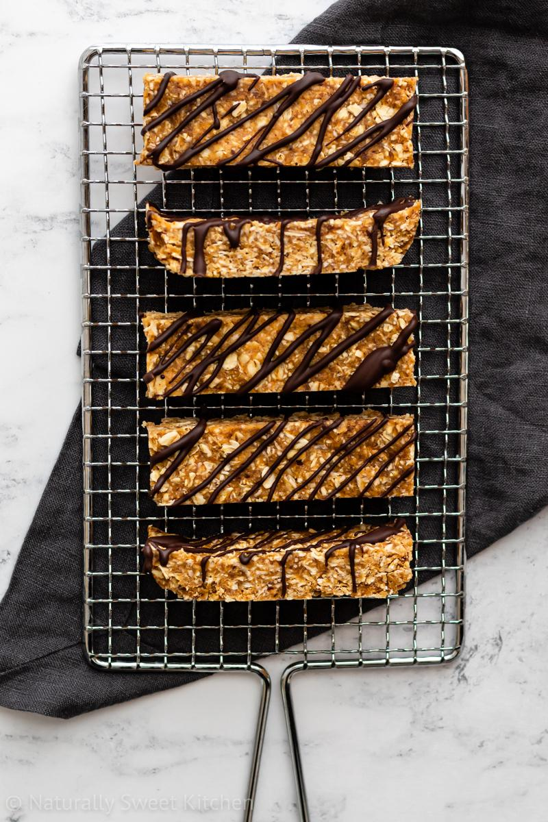 a small batch of peanut butter flapjacks being served on a silver wire rack with a dark grey linen underneath