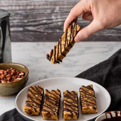 Someone taking a no sugar peanut butter flapjack off of a serving plate. there is a coffee carafe and bowl of peanuts in the background