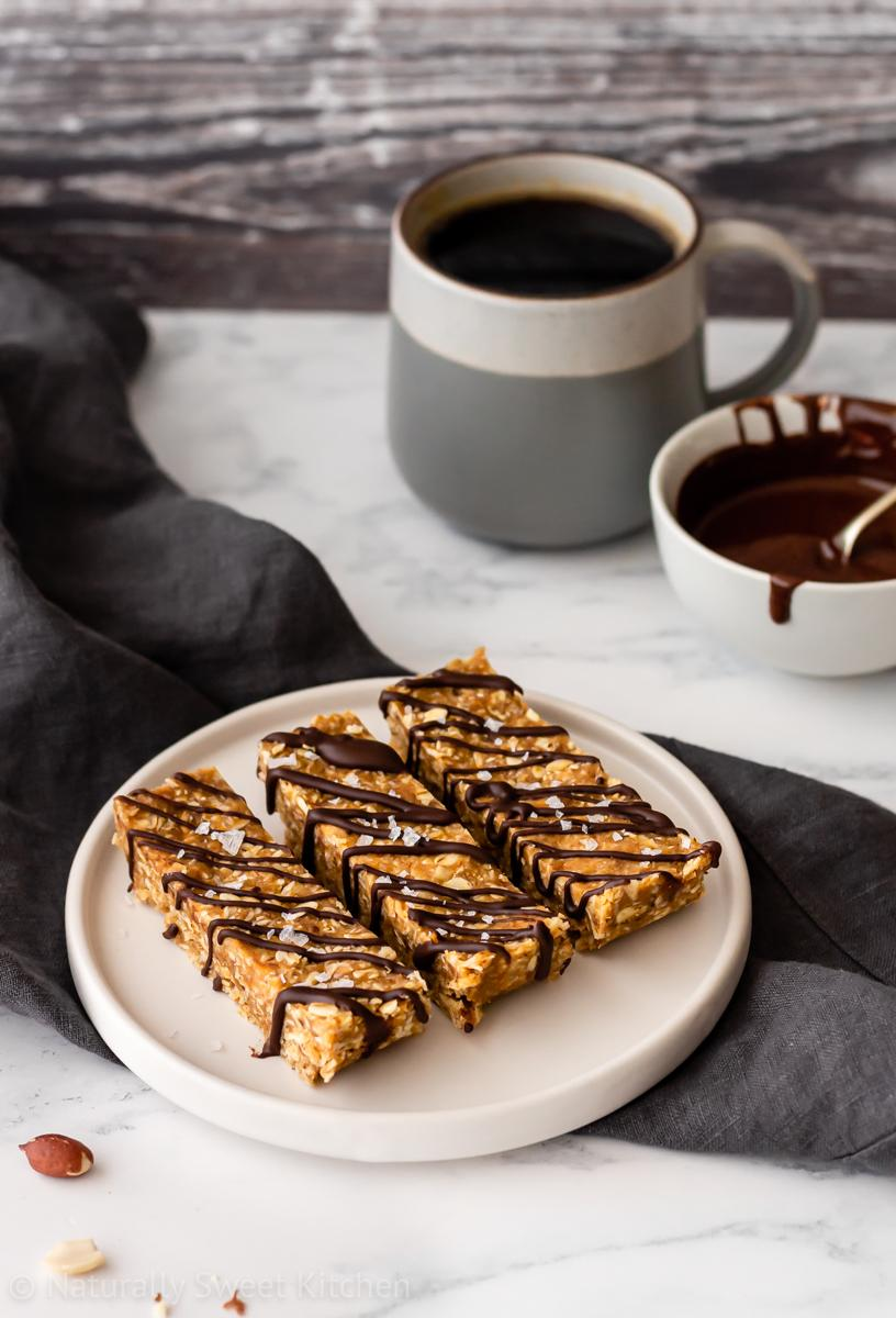 A serving plate with three no bake peanut butter flapjacks topped with drizzles of chocolate. there is a mug of coffee and bowl of melted chocolate in the background.