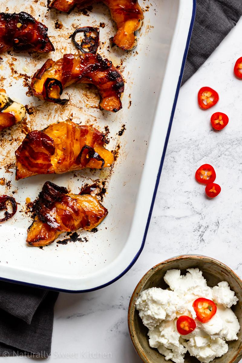 hot roasted acorn squash slices wrapped in bacon in a baking tray on a marble table with a bowl of goats cheese and red chilli slices on the side.