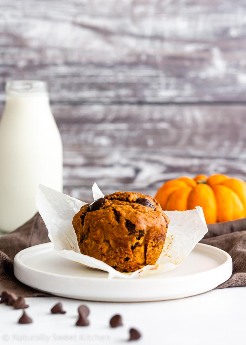 a pumpkin chocolate chip muffin with the wrapper partially unfolded on a white plate with a bottle of milk and small munchkin pumpkin in the background