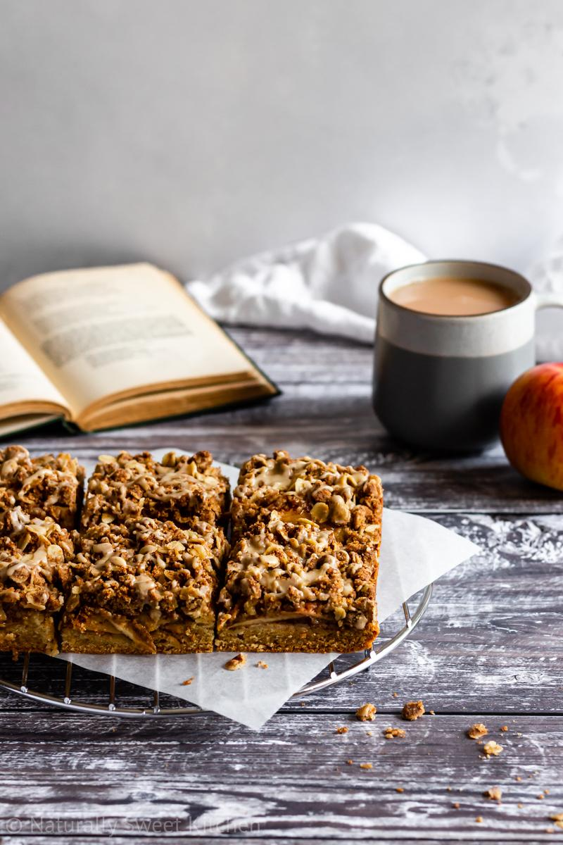 six apple slice squares are sitting on a silver wire rack. there is a book, mug of tea, and red apple in the background