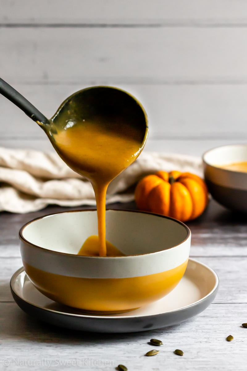 a ladle serving up a bowl of dairy free roasted pumpkin soup. there is a second bowl of soup in the background with a munchkin pumpkin beside it and a beige linen napkin in the background.