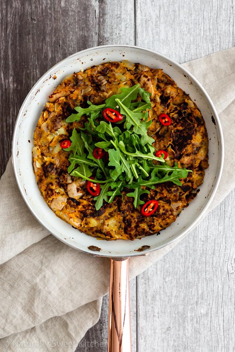 a white skillet contains a small-batch bubble and squeak made from sausage and pumpkin. it is topped with rocket and fresh red chilli slices.