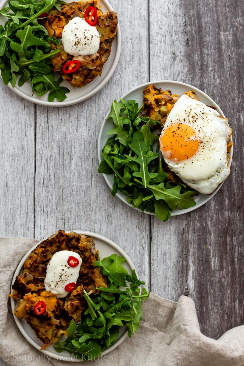 Three small plates of pumpkin bubble and squeak. two are topped with sour cream and one is topped with a runny egg.