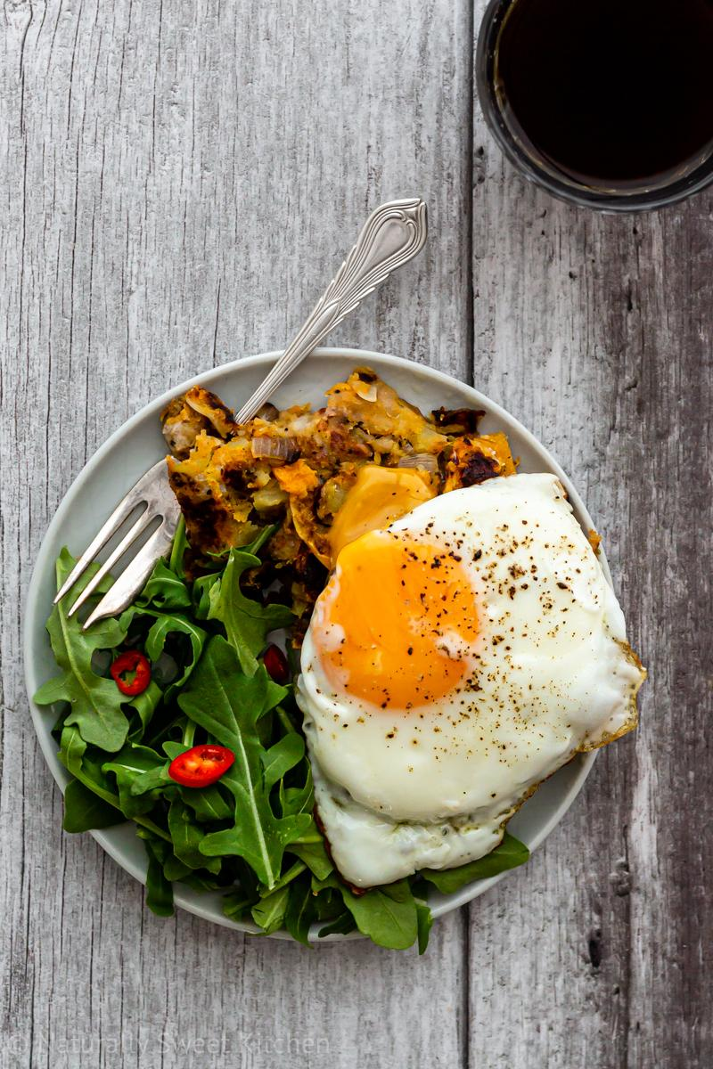 A plate of bubble and squeak made from sausage and pumpkin topped with a runny egg and served with rocket