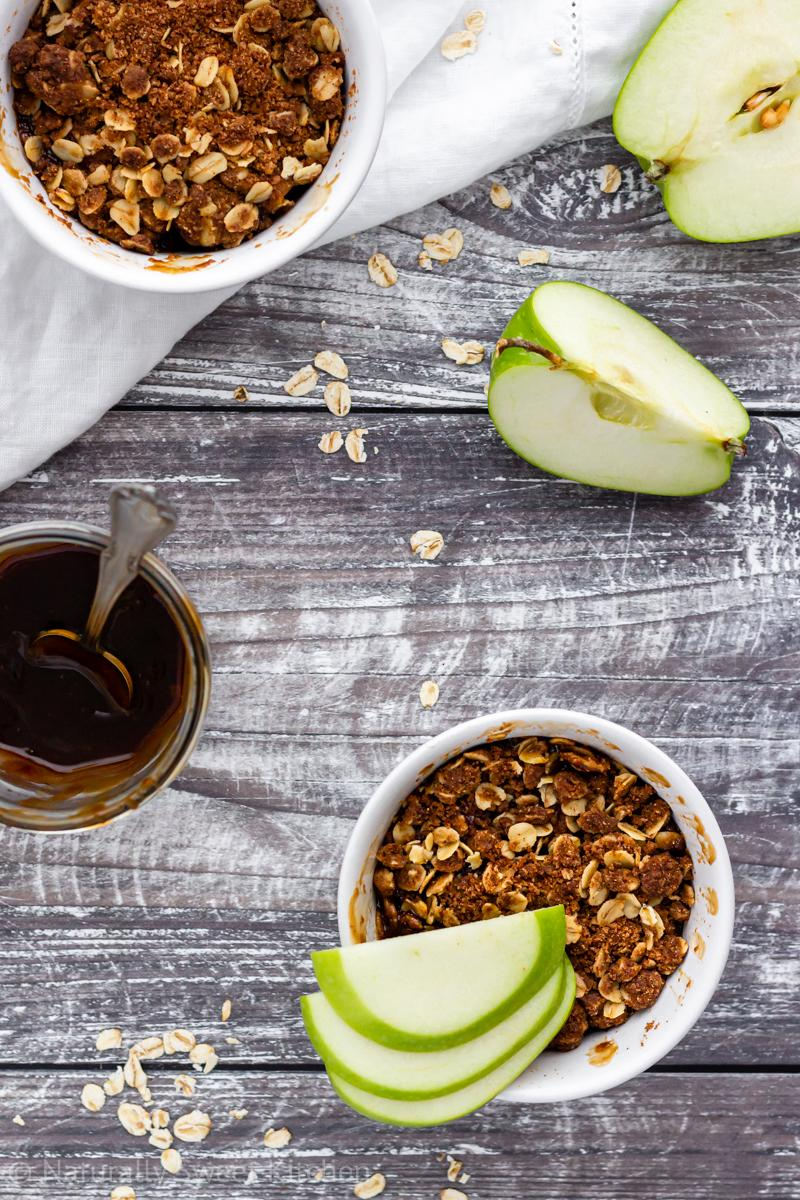 two refined sugar free apple crumbles on a wooden table surrounded by a white linen napkin, green apples, and a jar of salted caramel sauce.