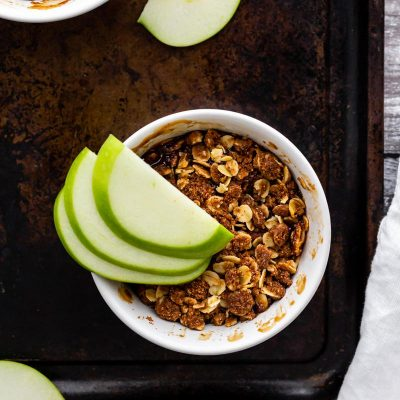 A serving of caramel apple crumble on a dark serving tray topped with green apple slices
