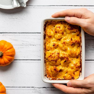 hands are serving a dish of small batch pumpkin cauliflower cheese on a white wooden table