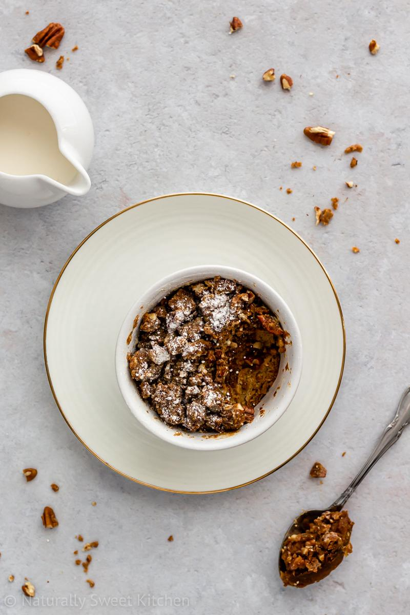 An aerial shot of an individual refined sugar free bread pudding recipe flavoured with pumpkin spice on a white plate with a spoonful taken out of it. there is a jug of cream in the upper left corner of the image and pecans scattered around