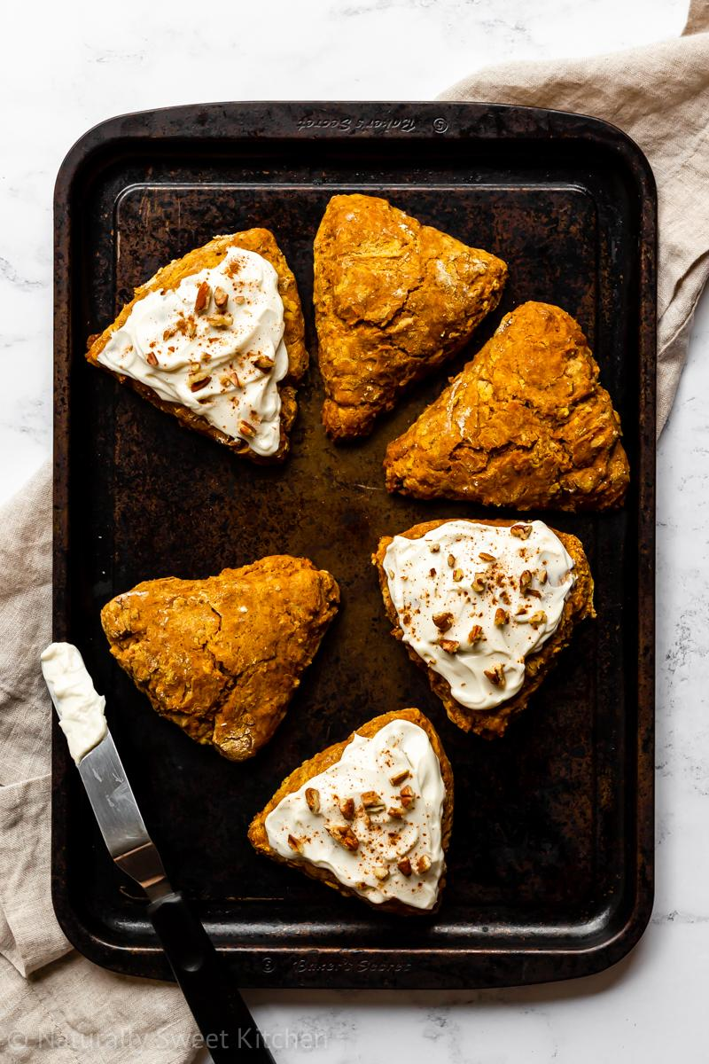 six refined sugar free pumpkin scones on a baking tray. three scones are frosted and topped with pecans and three are plain