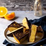 a platter of chocolate orange shortbread bars are arranged on a blue linen napkin surrounded by cut up orange segments and holiday decorations