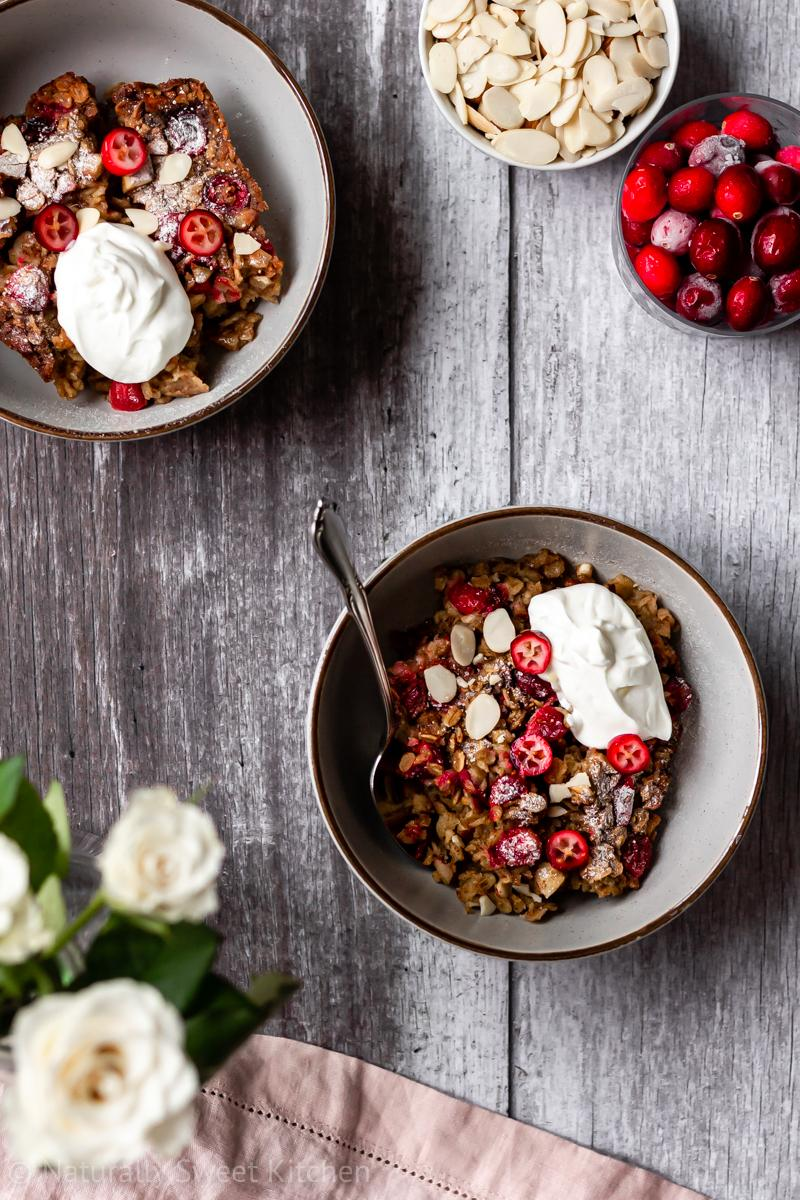 two servings of cranberry baked oats in grey bowls on a wooden table topped with flaked almonds and plain yoghurt.
